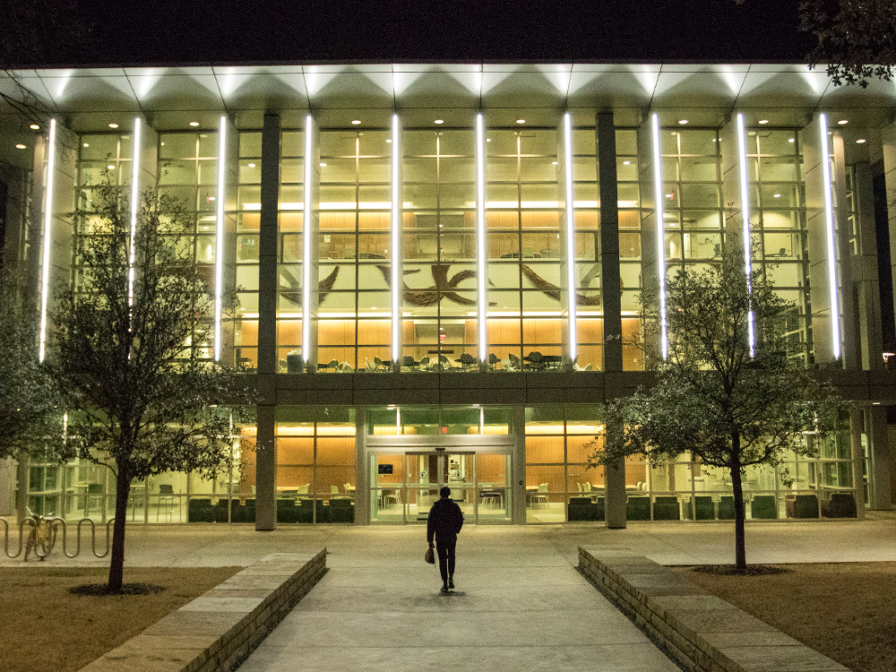 A lone student walks toward a lit-up Founders Building at night