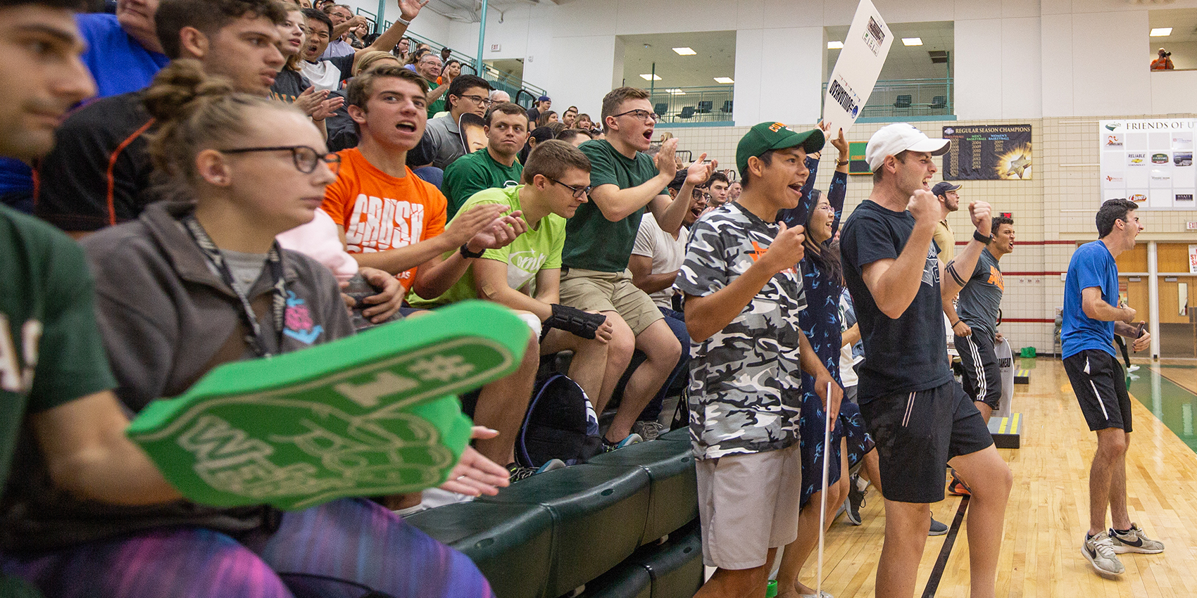 Students cheering on a team in a gymnasium
