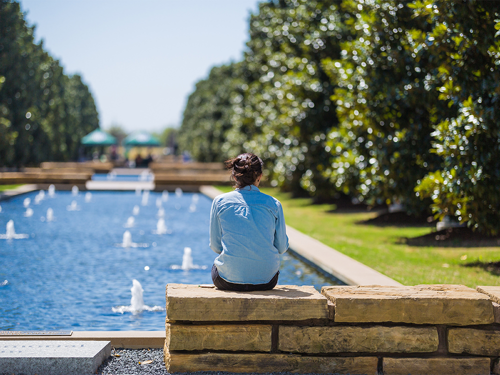 Woman sitting on stone slap by reflecting pools