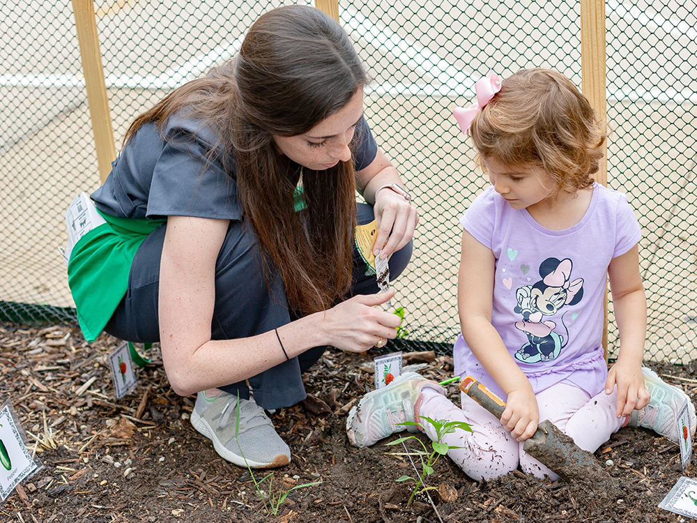 College student and young girl plant vegetables