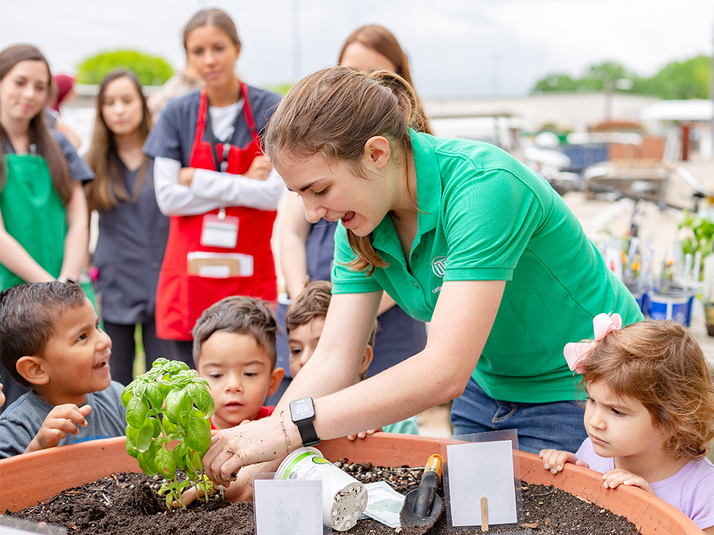 College student planting flowers with young children