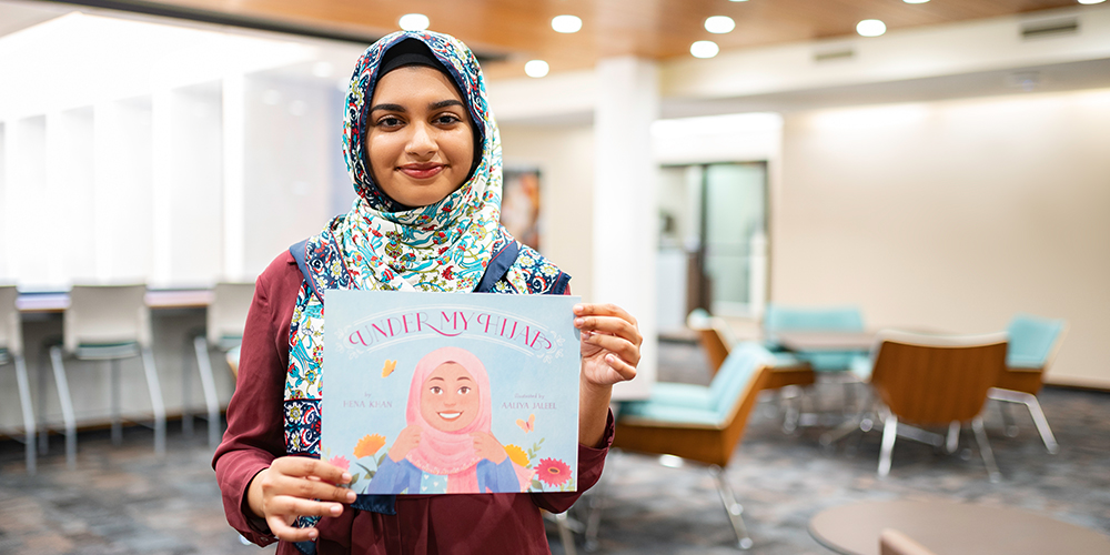 Woman wearing a hijab holding a book she illustrated