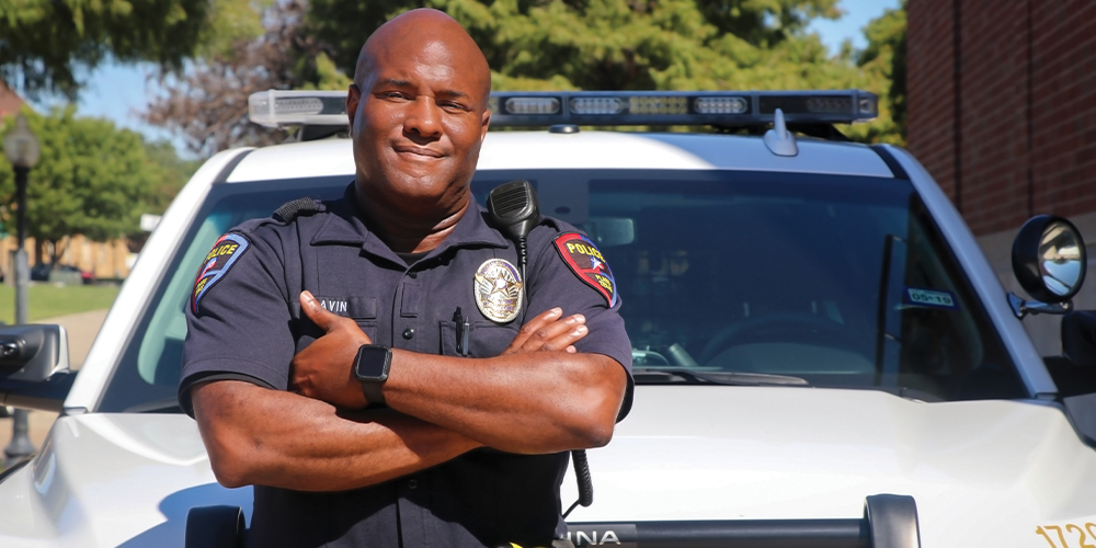 Black police officer with folded arm poses in front of his squad car