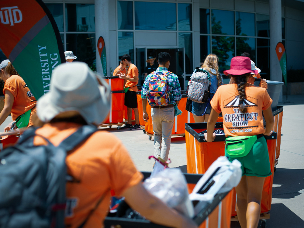 Line of volunteers with carts of student luggage