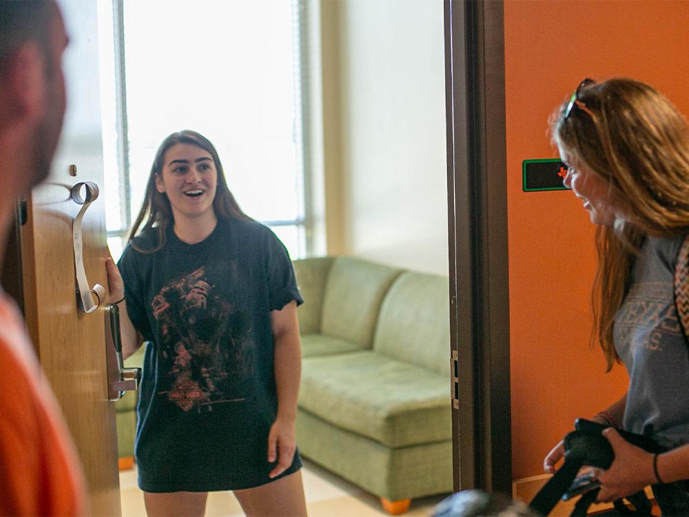 Female student opening door to meet roommate