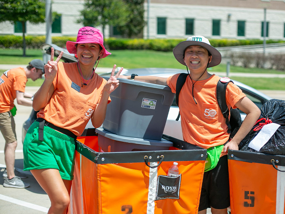Student workers pause for a photo while loading up luggage in carts