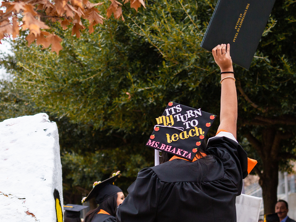 Woman waving diploma holder with a cap that says it's my turn to teach