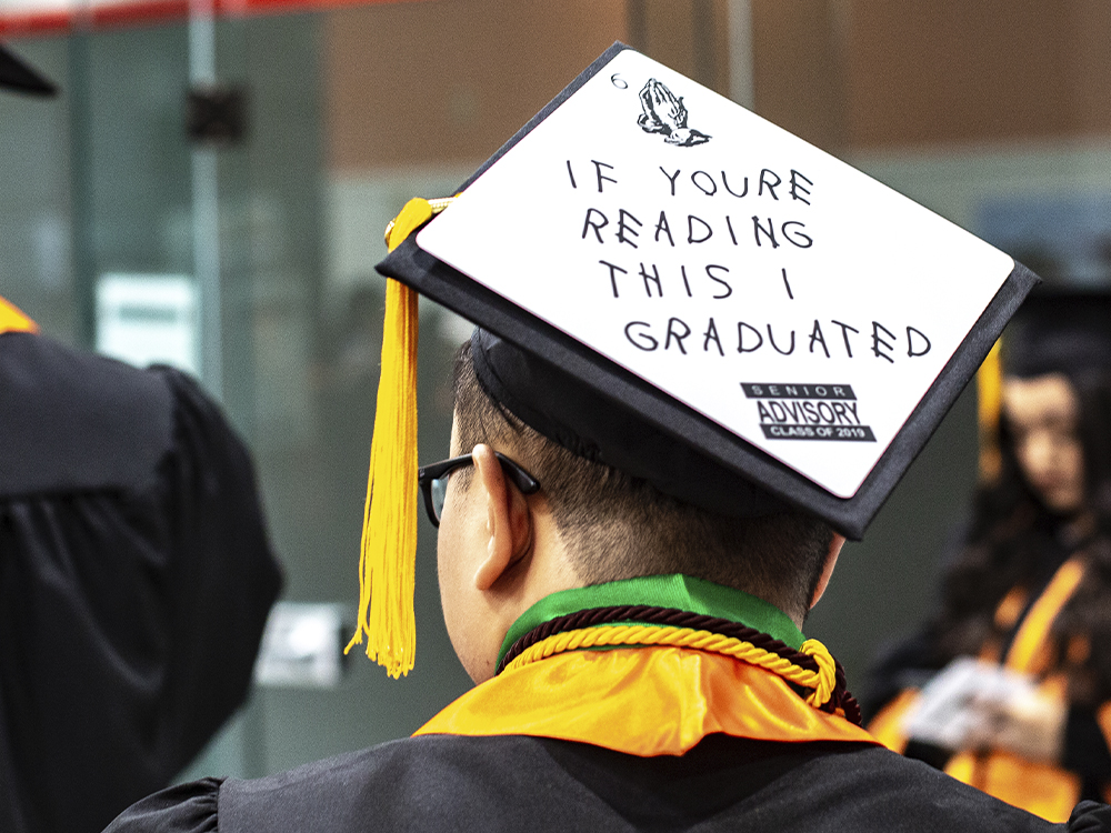 Man wearing cap that says If you're reading this I graduated