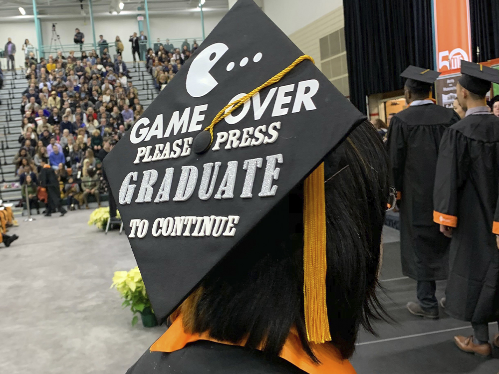 Woman wearing a cap that says game over, please press gradute to continue
