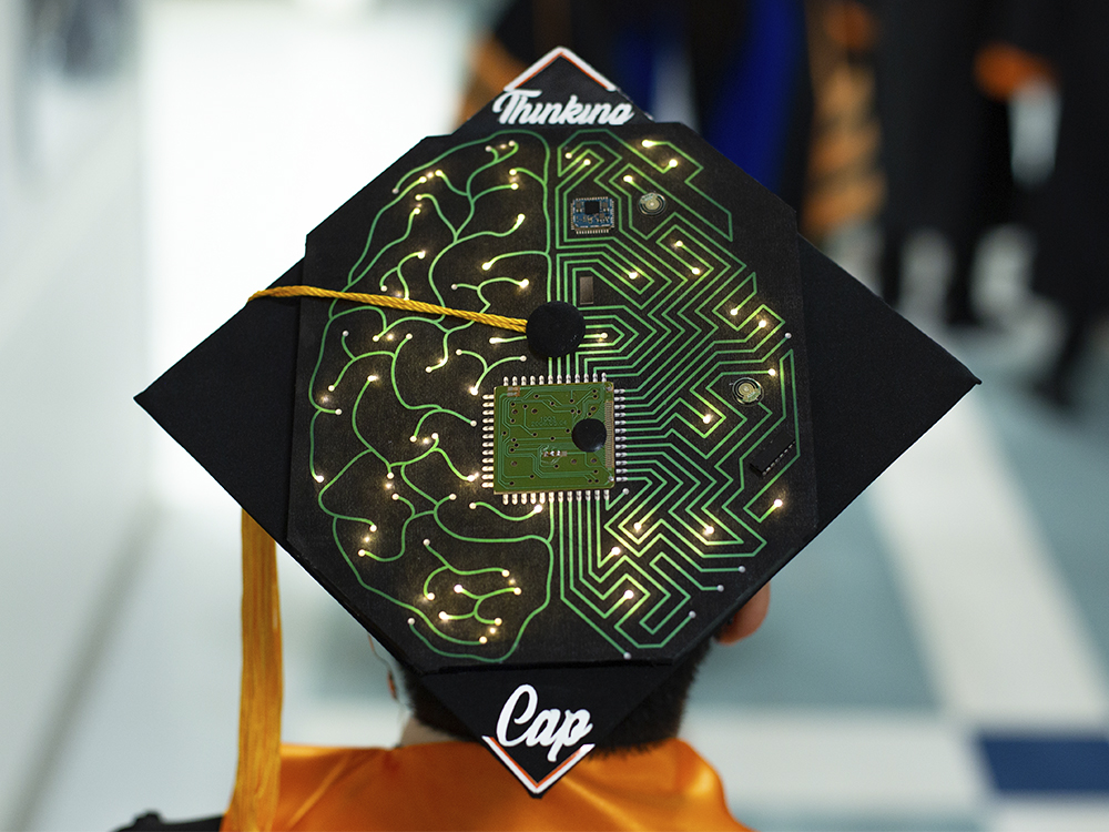 Man wearing cap that says thinking cap and has an image of a brain as a circuit board