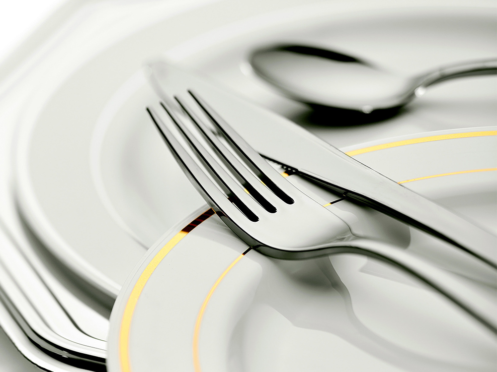 A fork, knife and spoon sit atop an empty white plate