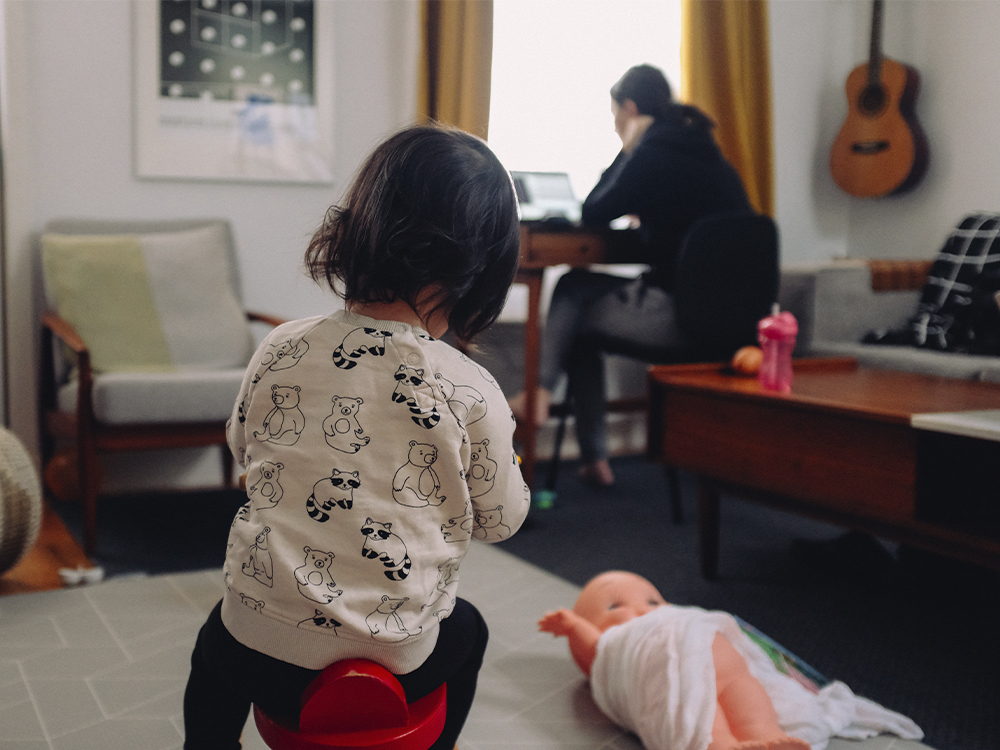 A girl plays in the foreground while their parent works on a computer in the background.