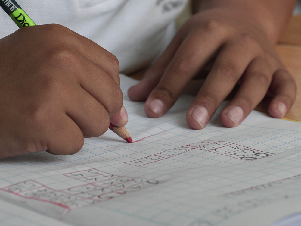 Young student fills out a math problem on a piece of paper with a red pencil
