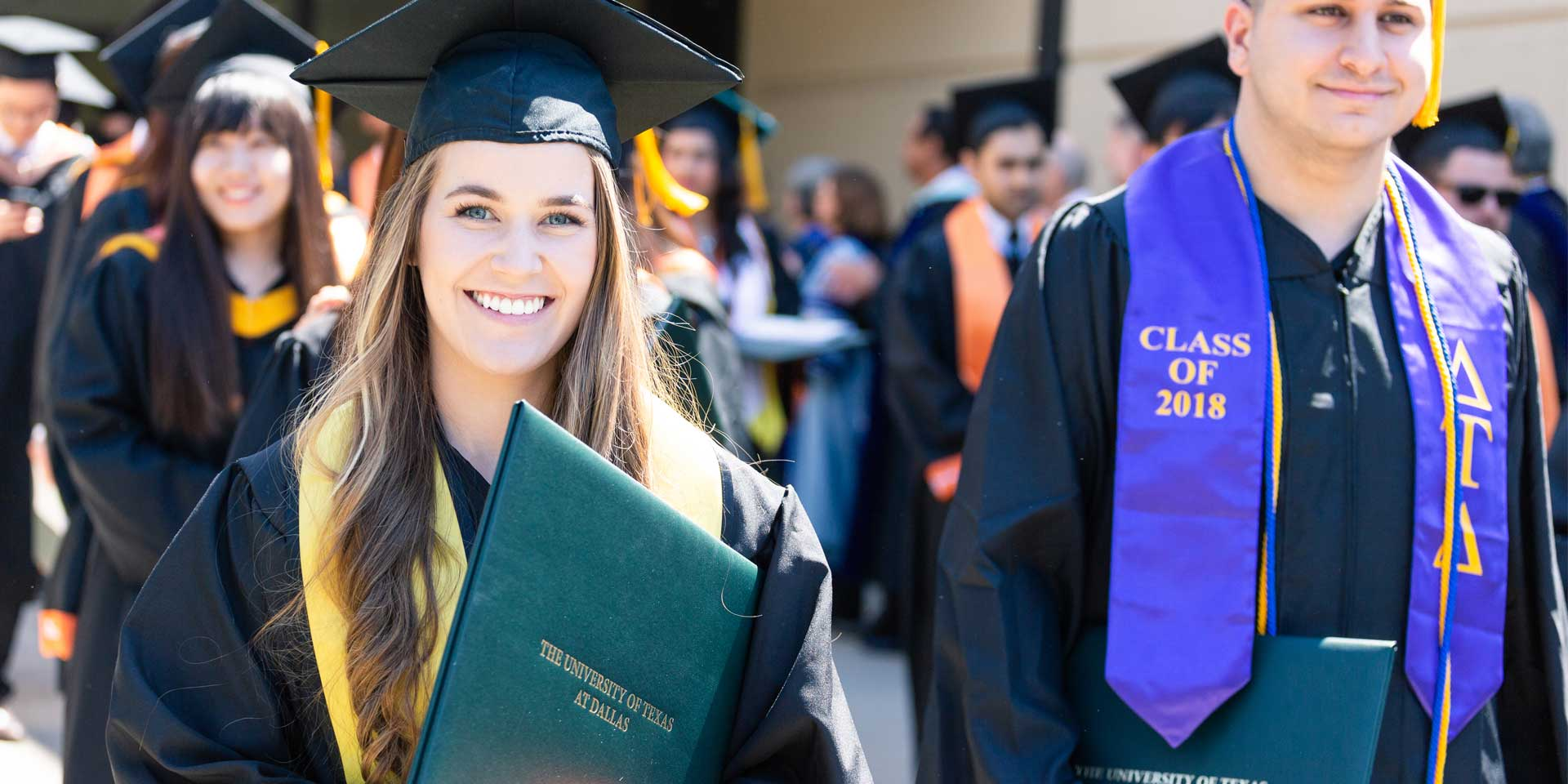 Megan Eckert grins widely after earning her bachelor's degree in finance.