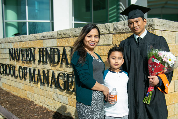 Bachelor's in Information Technology and Systems graduate with his family on UT Dallas commencement day