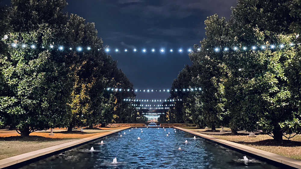 McDermott Mall at night with lights strung above the reflecting pools.