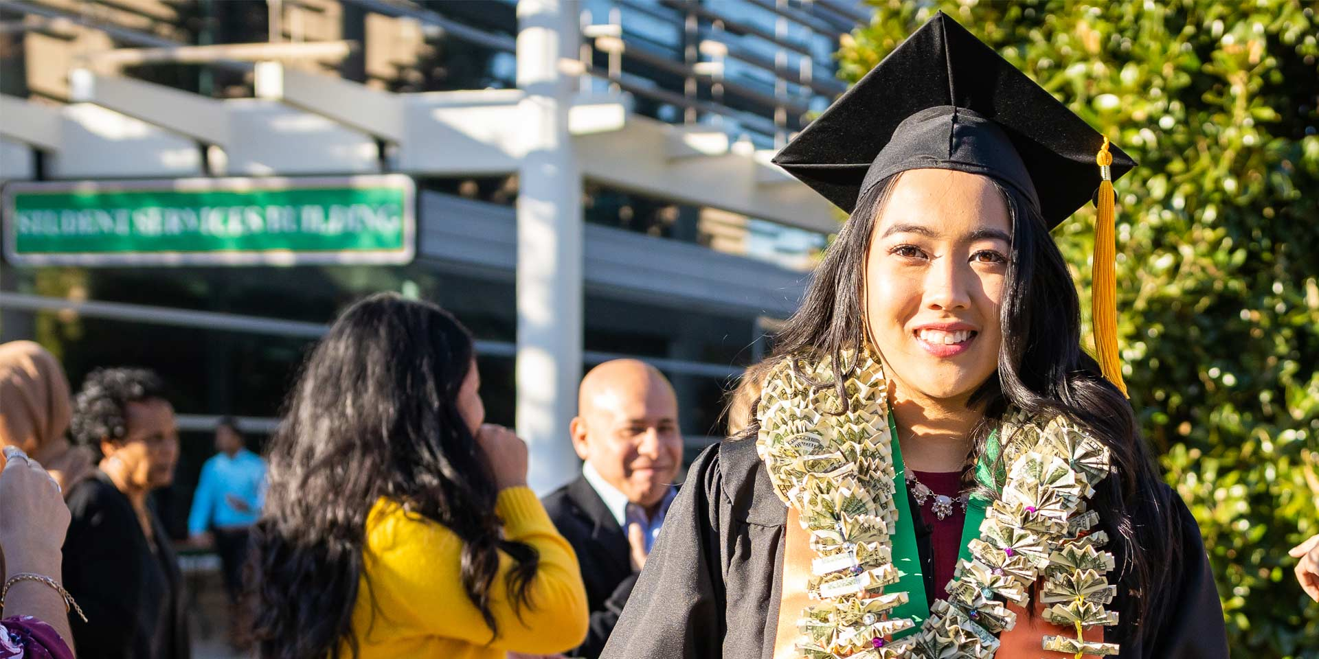Marisa Homan, who graduated with a bachelor's degree in healthcare management, wore a homemade lei made of money.