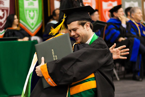 healthcare management student hugging professor at UT Dallas commencement