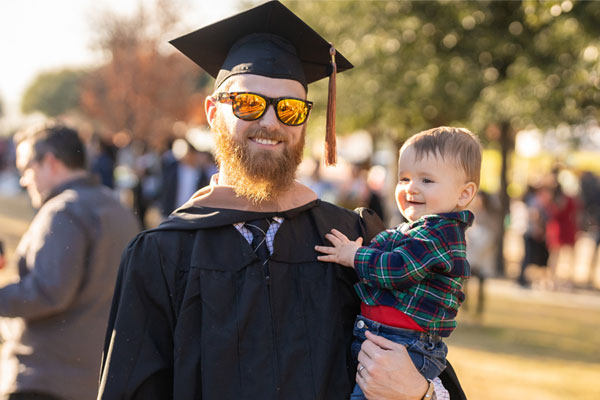 ut dallas jindal school graduate holding his child on commencement day