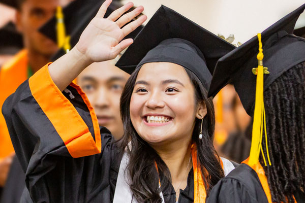 happy jindal school undergraduate waving in her cap and gown on ut dallas commencement