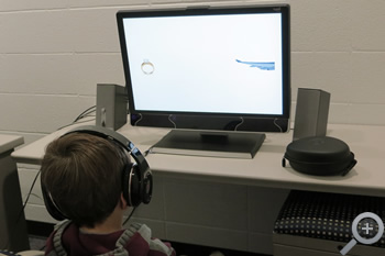 Young research participant works with computer program on speech testing